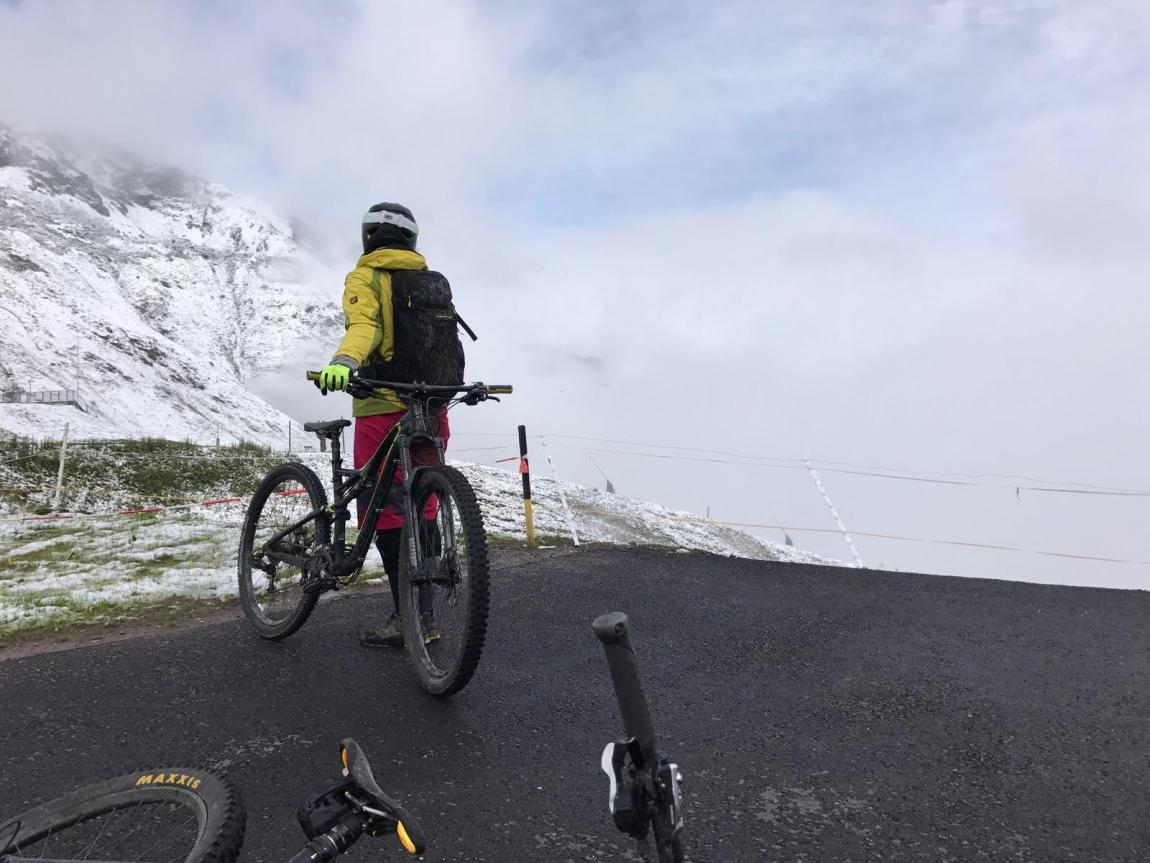 female mountain biker looking into the valley next to snowy mountains