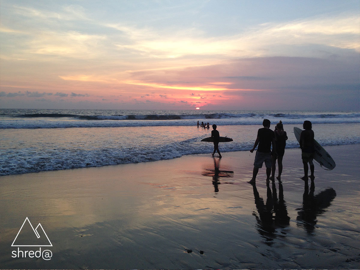 surfers watching the waves and sunset at echo beach in bali
