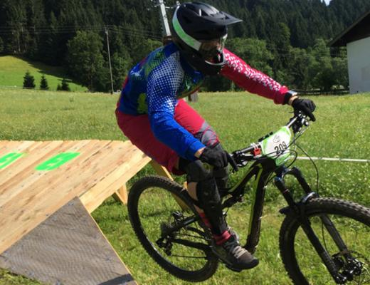 female mountainbiker jumping from a wooden ramp