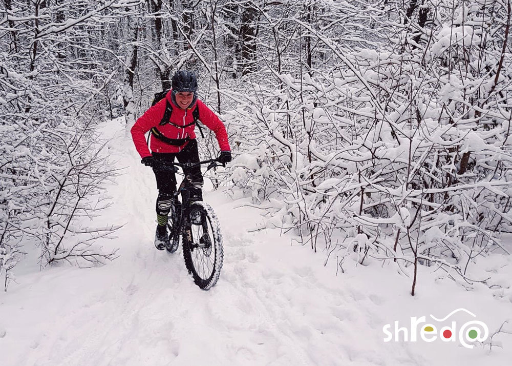 female mountain biker riding through the snow