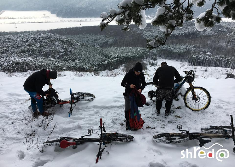 mountain bikers in the snow getting ready for the downhill