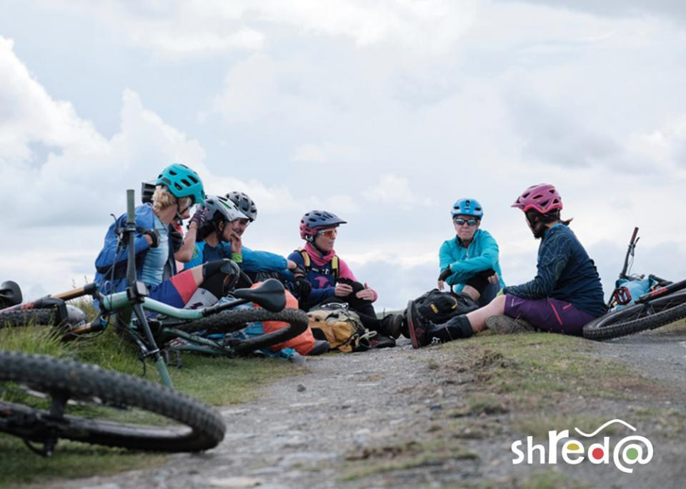 group of female mountain bikers sitting on the ground and talking with each other