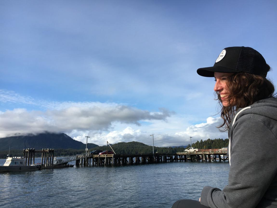 female sitting at the docks of Tofino on Vancouver Island looking into the sun smiling