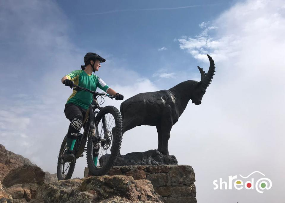 female mountain biker with capricorn statue at piz nair